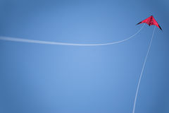 Blue sky, red kite flies high. White strings. Stock Photos