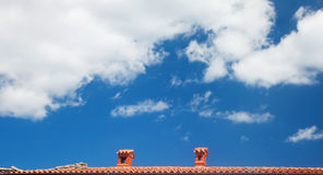 Blue sky with red roof line. Blue sky with dramatic clouds and red roof line of classic tiles with two chimney caps Royalty Free Stock Photography