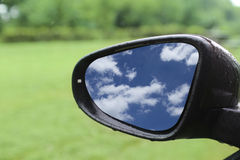 Blue sky reflected in car rear mirror Stock Photo