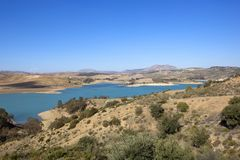 Blue sky reflected in a lake in Andalucia. A blue lake in sandy arid mountainous scenery with trees and wind turbines under a blue sky in andalucia spain Stock Photography
