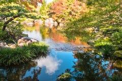 Blue sky reflected in the lake at Koko-en Garden, Himeji, Japan. Blue sky with clouds and autumn colors from the trees reflected in the lake at Koko-en Garden, a stock photography
