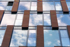 Blue sky reflected in mirror windows of modern office building. Blue overcast sky and clouds reflected in mirror windows of new modern office building with one Stock Photos