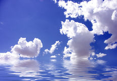 Blue Sky Reflected in Water. Bright Blue Sky and Puffy White Clouds Reflected in Water Stock Photo