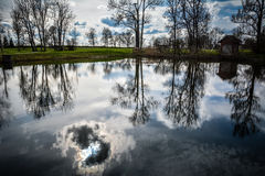 Blue sky reflecting in water. Beautiful blue sky with clouds and trees reflecting in pond/ water. Nice background. Shot in Latvia Stock Photo