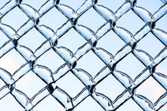Blue Sky Refracted by Ice on a Metal Chain Link Fence Stock Photos