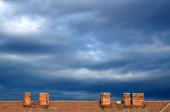 Blue sky and roof. The sky at evening with dark clouds Royalty Free Stock Photos