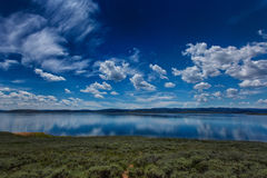 Blue Sky's Blue Water. Panoramic view of Strawberry Reservoir in Utah USA with still waters and a partly cloudy sky's in July. Look close you can see a scorpio royalty free stock image