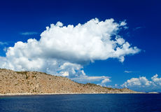 Blue sky and sea landscape with mountains white clouds in horizon Royalty Free Stock Photography
