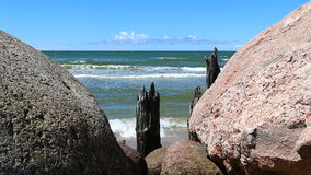 Blue sky and sea view through gap between stones stock footage