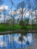 Blue sky with small cloud reflect in small pond. In early spring royalty free stock photography