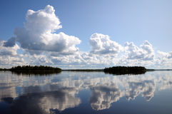 Blue sky and small clouds above the mirrored lake. The picture shows typical landscape in the south region of Karelia - blue sky, clouds, big lake looks like a stock photo