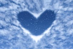 Blue sky with snow and clouds in heart shape. Happy and love background. Love stock photography