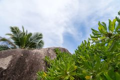 Blue sky with some clouds and big stones in front. On Seychelles Royalty Free Stock Photography