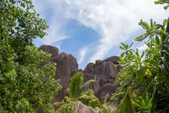 Blue sky with some clouds and big stones in front. On Seychelles Royalty Free Stock Image