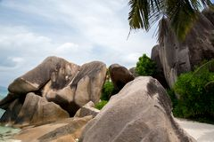Blue sky with some clouds and big stones in front. On Seychelles Stock Image