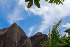 Blue sky with some clouds and big stones in front. On Seychelles Stock Images
