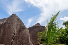 Blue sky with some clouds and big stones in front. On Seychelles Stock Photo