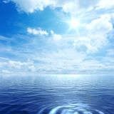 Blue sky with some clouds. And the sun over the ocean royalty free stock photo