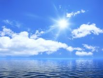 Blue sky with some clouds. And the sun over the ocean royalty free stock photography