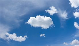 Blue sky with some white clouds scattered across. Blue sky with some white fluffy clouds scattered across it royalty free stock photos