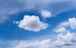 Blue sky with some white clouds scattered across. Blue sky with some white fluffy clouds scattered across it stock image