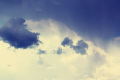 Blue sky with some white puffy clouds. Toned in retro style Royalty Free Stock Photos
