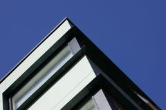 Looking up at a corner of a modern steel building set against a crisp blue sky royalty free stock image
