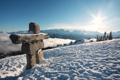 Blue Sky Stone Man. An inukshuk and a sun flare over Whistler and Blackcomb mountains, British Columbia, Canada Royalty Free Stock Photo