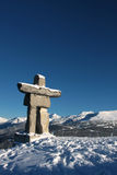 Blue Sky Stone Man. An Inukshuk (symbol of the 2010 winter olympic games and a traditional native sculpture) stands on Whistler mountain overlooking Blackcomb Royalty Free Stock Photos