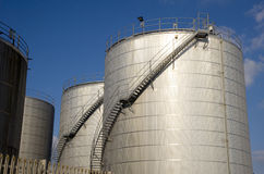 Blue sky and oil storage tanks Stock Image