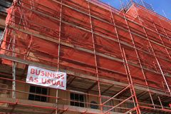 Store, business as usual under construction in the summer. Blue sky and the store is covered with a red network with the banner and the words, business as usual Royalty Free Stock Image