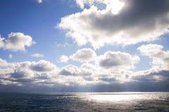 Blue sky, storm clouds, sunlight on the ocean Stock Photos