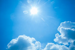 Blue sky with sun and clouds Stock Image