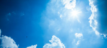 Blue sky with sun and clouds Stock Photo