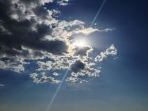 Blue sky with Sun flare through the clouds Royalty Free Stock Photos