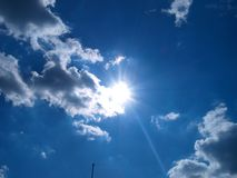 Sun illuminates the clouds. Blue sky, the sun illuminates the clouds royalty free stock image