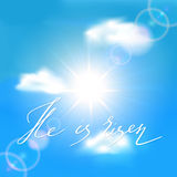 Blue sky with sun and lettering He is risen Royalty Free Stock Photo
