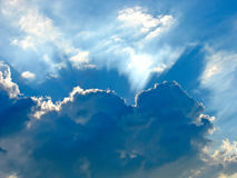 Blue sky with sun rays through the clouds Stock Image