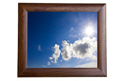 Blue sky and sun in Wooden picture frame. Isolate on white background Royalty Free Stock Photography
