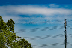 Blue sky on sunny day with high voltage electric power supply pole Royalty Free Stock Photo