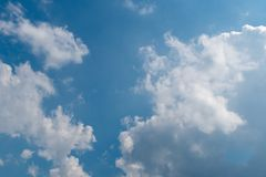 Blue sky in sunny day with white puffy clouds. Natural background royalty free stock image