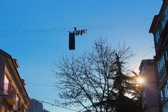 Blue sky, drying clothes. Blue sky, sunrays, drying underwear, hanging dress, on a clothespin, you can see a tree, houses, Crimea Stock Image