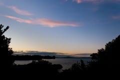 Blue sky sunset clouds over dark coastal landscape Stock Photos