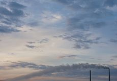 Blue sky at sunset with elements of a power station. Blue sky with pipes of thermal power station Royalty Free Stock Photo
