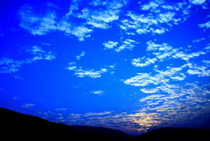 Blue sky and sunset with peacefull cotton clouds Stock Photos