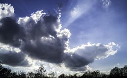 Sunlight behind clouds in blue sky. Blue sky with sunshine behind white clouds Royalty Free Stock Image