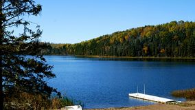 Blue sky with sunshine over beautiful serene remote northern Minnesota lake. With autumn colors, boat, dock and new snow stock video footage