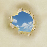 Blue sky through torn hole. Torn hole in paper background revealing blue sky and cloudscape background, freedom concept royalty free stock photos