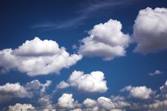 The blue sky is tucked in a lot of white fluffy clouds.  stock photos
