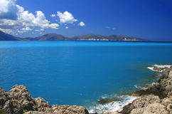 Blue sky turquoise sea. Blue sky and turquoise sea landscape with mountains and white clouds in horizon Stock Images